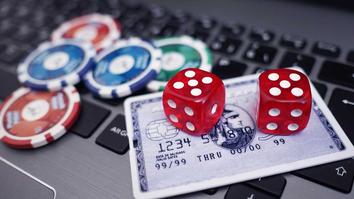 online casino payout laptop with credit card and dice